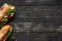 在黑暗的木背景的两条金枪鱼三明治 库存照片