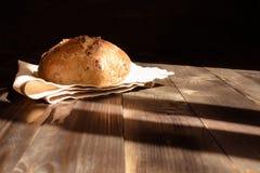 在黑暗的木背景的新鲜的家制面包 库存图片