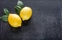 在黑暗的木背景的新鲜的柠檬 免版税图库摄影
