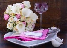 在黑暗的木背景的桃红色题材婚礼表设置 免版税库存照片