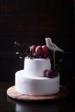 在黑暗的木背景的白色两层蛋糕与黑暗的光 库存照片