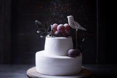 在黑暗的木背景的白色两层蛋糕与黑暗的光 免版税库存照片