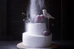 在黑暗的木背景的白色两层蛋糕与黑暗的光 免版税库存图片