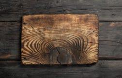 在黑暗的木背景的空的厨房板 免版税库存图片
