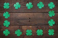 在黑暗的木背景的纸绿色三叶草三叶草叶子框架 免版税库存照片