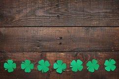 在黑暗的木背景的纸绿色三叶草三叶草叶子边界 免版税库存图片