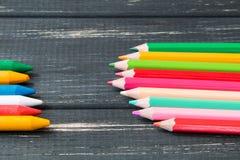 在黑暗的木背景的色的铅笔 免版税图库摄影
