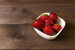 在黑暗的木背景的草莓 横幅蝶粉花瓢虫草坪夏天 健康的食物 免版税库存图片
