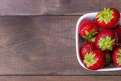 在黑暗的木背景的草莓 背景庭院查出的草莓白色 图库摄影