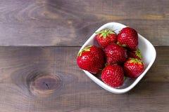 在黑暗的木背景的草莓 背景庭院查出的草莓白色 免版税库存照片