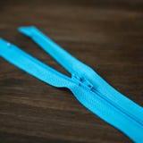 在黑暗的木背景的蓝色拉链 免版税库存照片