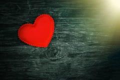 在黑暗的木背景的装饰心脏与从窗口的明亮的白光 库存照片