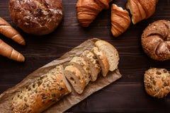 在黑暗的木背景顶视图的新鲜的切的面包 库存照片