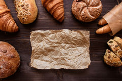 在黑暗的木背景顶视图的新鲜面包 免版税库存图片
