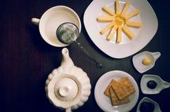 在黑暗的木表面上的恒星形成组织的buiscuits板材和乳酪在茶壶旁边,小板材与 免版税库存图片