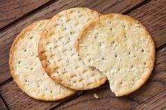 在黑暗的木头的三个金黄乳酪薄脆饼干 库存照片