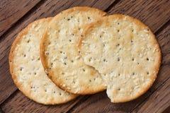 在黑暗的木头的三个金黄乳酪薄脆饼干 免版税库存照片