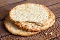 在黑暗的木头的三个金黄乳酪薄脆饼干 免版税图库摄影
