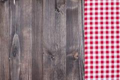 在黑暗的木头的红色格子花呢披肩布料 免版税库存图片