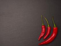 在黑暗的板岩背景的红色意大利辣味香肠 库存图片
