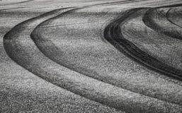 在黑暗的柏油路的弯曲的轮胎轨道 免版税图库摄影