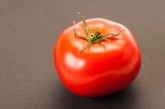 在黑暗的桌或背景上的一个唯一完善的红色蕃茄 库存照片
