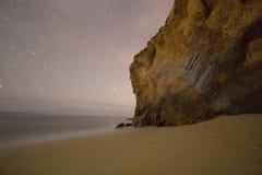 在黑暗的沿海岩石与星落后 免版税库存照片