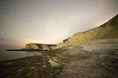 在黑暗的沿海岩石与星落后 库存图片
