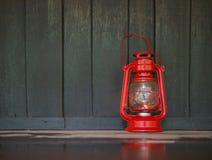 在黑暗的湿木地板上的一个红色老灯笼与反射o 免版税库存图片