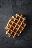 在黑暗的石背景垂直的比利时华夫饼干 免版税图库摄影