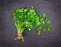 在黑暗的石背景的新鲜的绿色荷兰芹 免版税图库摄影