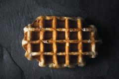 在黑暗的石背景顶视图的比利时华夫饼干 库存图片