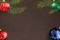 在黑暗的红色波浪,蓝色和绿色有肋骨球与圣诞节冷杉分支 图库摄影