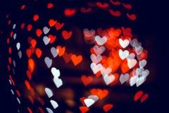 在黑暗的纹理的红色和白色心脏bokeh用于图形设计 免版税库存照片