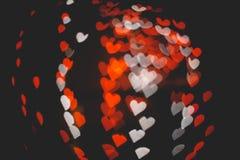 在黑暗的纹理的红色和白色心脏bokeh用于图形设计 免版税库存图片