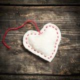 在黑暗的老委员会的五颜六色的被编织的心脏 免版税库存图片
