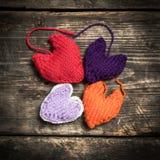 在黑暗的老委员会的五颜六色的被编织的心脏 库存照片
