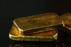 在黑暗的背景上把放的金制马上的齿龈 免版税库存照片