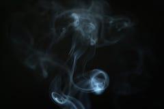 在黑暗的背景特写镜头的奥秘蓝色烟 免版税库存照片