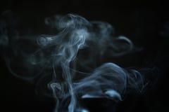 在黑暗的背景特写镜头的奥秘蓝色烟 免版税库存图片