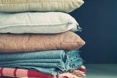 在黑暗的背景的五颜六色的枕头堆 免版税图库摄影