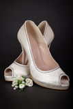 在黑暗的背景的典雅的白色女性鞋子 新娘现有量行程穿上鞋子妇女年轻人 免版税库存图片