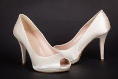 在黑暗的背景的典雅的白色女性鞋子 免版税库存照片