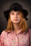 戴在黑暗的背景的典雅的青少年的女孩黑帽会议 青年时尚 免版税库存照片