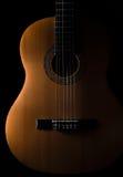 在黑暗的背景的古典吉他 免版税库存照片