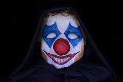 在黑暗的背景的可怕小丑面具 图库摄影