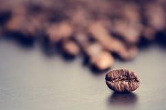 在黑暗的背景的咖啡豆 原始豆的咖啡 成颗粒状的产品 热的饮料关闭 图库摄影