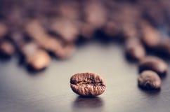 在黑暗的背景的咖啡豆 原始豆的咖啡 成颗粒状的产品 热的饮料关闭 库存图片
