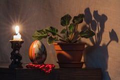 在黑暗的背景的复活节彩蛋在烛光 库存图片