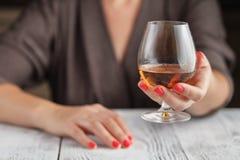 在黑暗的背景的妇女饮用的酒精 在酒杯的焦点 库存照片